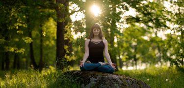 Conceito de exercício de vida saudável de meditação. Mulher caucasiana desportiva apta fazendo ioga ao ar livre. meditando e relaxando em Padmasana Lótus Pose